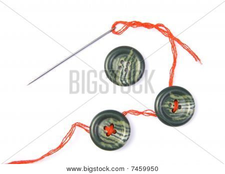 Sewing Needle With Red Thread And Buttons