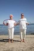 Outdoor photo of retired couple with hula-hoops and silly glasses poster