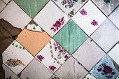 Surface of the old and partly damaged square tiles with different design. poster