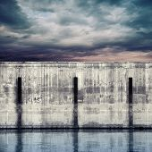 Abstract port fragment. Gray concrete mooring wall with dark stormy sky poster