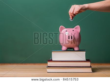 Person Depositing Money In A Piggy Bank On Top Of Books With Chalkboard