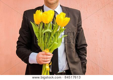 A man wearing a business suit, holding a bouquet of yellow tulips.