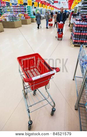 Empty Red Shopping Cart In The Interior Of Auchan Store