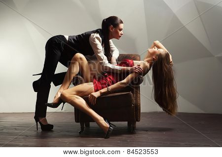 Beautiful Lesbian Flirting Couple On The Chair.