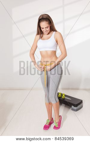 Woman Measuring Her Waistline With A Measuring Tape