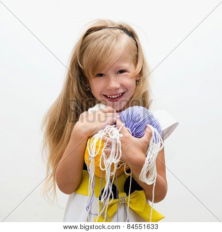 Portrait of a pretty little blonde girl with yarn. poster