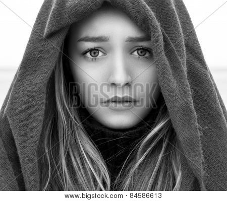 black and white portrait of a beautiful young girl with big eyes with a sad mood sadness on her face