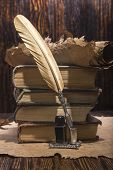 Vintage golden pen and ancient manuscripts on a wooden background poster