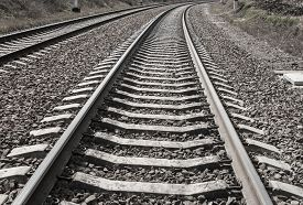Railroad tracks sleepers on gravel monochrome