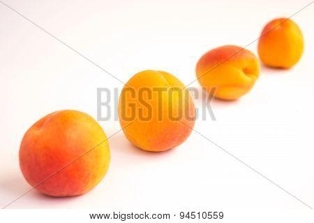 Apricots Arranged Diagonally on White Background
