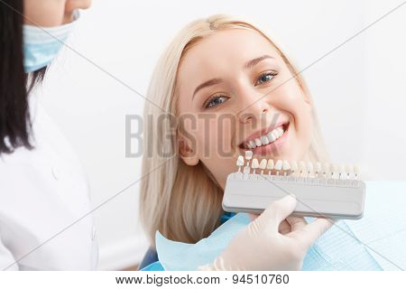 Dentist matching filling for teeth of his client