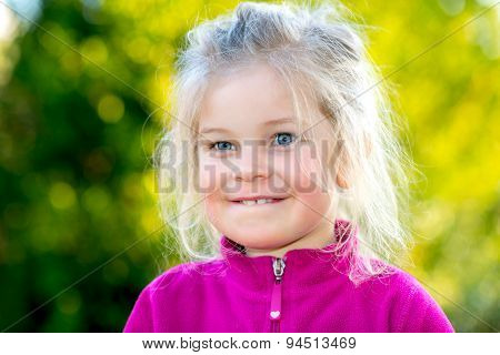 Little Smiling Girl In Front Of Nature Background