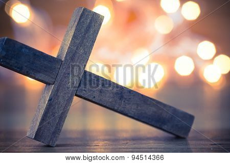 A wooden Christian cross with a soft bokeh lights background. poster