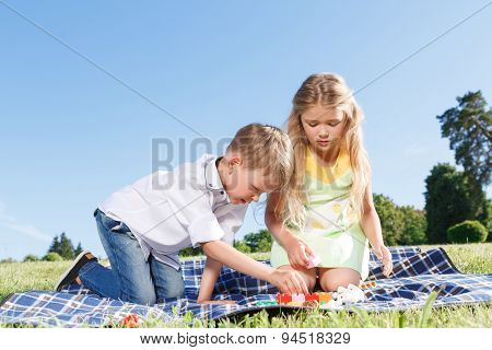 Lets play . Nice little friend playing with erector set  and having fun while sitting on the blanket. poster