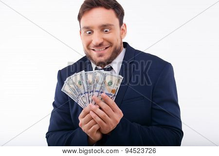 Cheerful young guy is crazy about dollars