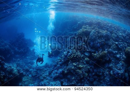 Underwater shot of two divers exploring underwater canyon. Red Sea, Egypt