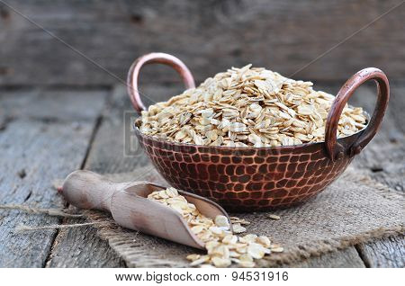 oat flakes in a copper plate on a wooden table poster