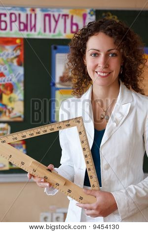 Portrait of schoolteacher in a white blouse in school. Girl with ruler in his hand standing at blackboard. Looks into camera. Vertical format. poster