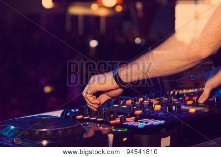 DJ hands on the remote. nightclub