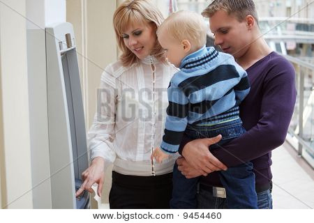 Young family with child receives money from cash dispense.