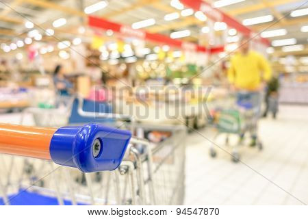 Blurred defocused grocery supermarket - Consumerism concept in period of economic crisis - Bright vivid blur of people in commercial center - Shallow depth of field with focus on shopping cart edge poster