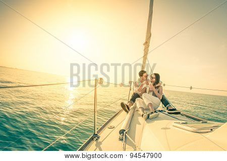Young Couple In Love On Sail Boat With Champagne At Sunset - Happy Exclusive Alternative Lifestye