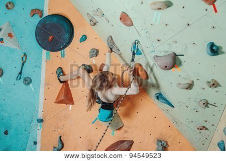 Girl In Safety Equipment Climbing In Gym