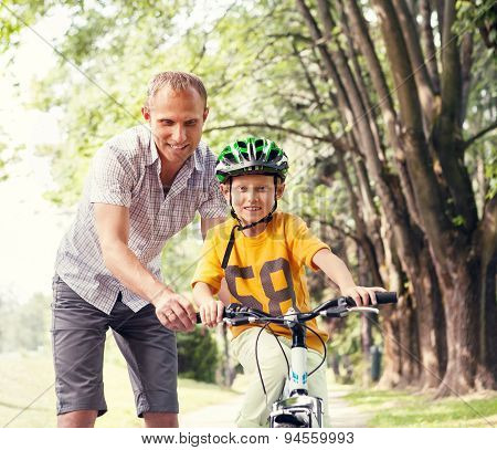 Father Learn His Son To Ride Bicykle