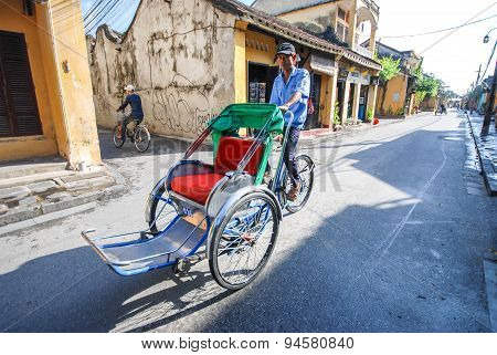 Man Riding A Traditional Cyclo In Hoi An