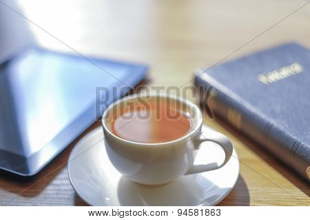 Near A Cup The Tablet And The Bible Lies.