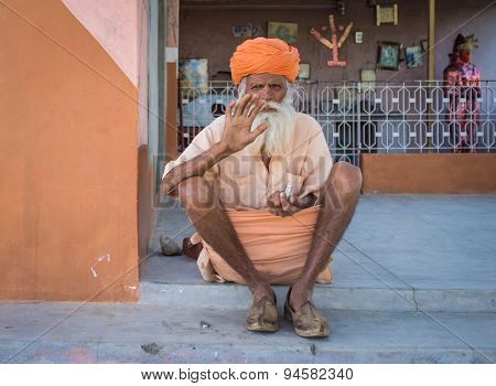 GODWAR, INDIA - 12 FEBRUARY 2015: Elderly Indian tribesman with turban in lungi sits on ground in front of temple and waves.