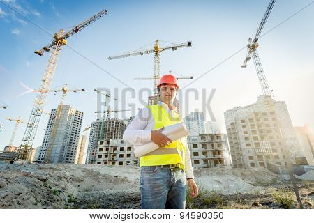 Construction Inspector Posing With Blueprints On Building Site