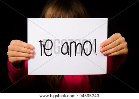 Studio shot of child holding a sign with Spanish words Te Amo - I Love You poster
