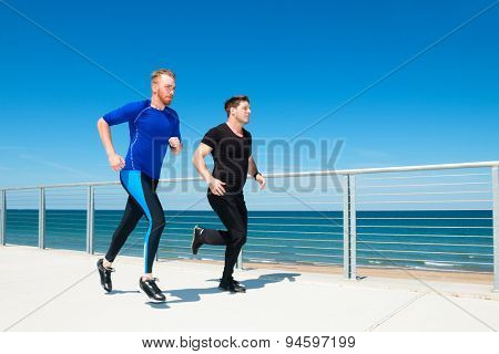 Two men running or jogging at a beachside park.