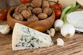 Horizontal photo of big portion on niva danish blue cheese in front of vegetable and bowl full of walnuts. Spring onion tomatoes camembert and garlic are around on wooden board. poster