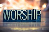 The word WORSHIP written in vintage metal letterpress type on a soft backlit background. poster