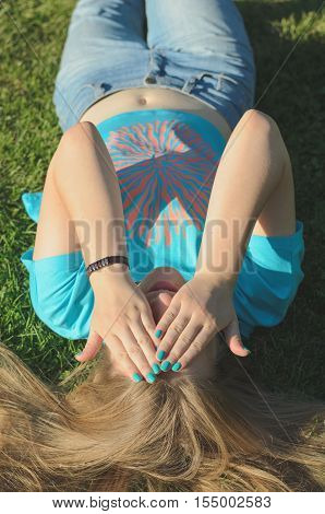 Young blond long-haired girl sitting on grass in a park in summer