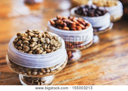 Various coffee beans on the wooden background.