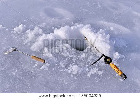 Hole in the ice and fishing rod lying in the snow
