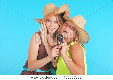 Two pretty thirteen year old girls wearing a big floppy straw sun hat isolated on blue