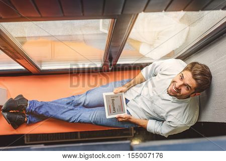 University life is great. Top view photo of young man posing at camera and smiling while enjoying digital tablet, sitting on cafe windowsill