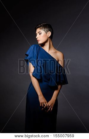 Young beautiful brunette girl in dark blue evening dress posing at party over grey background. Copy space. Eyes closed.