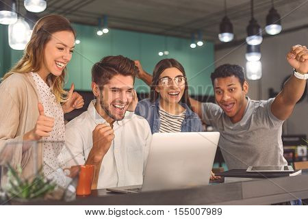 Having laugh between classes. Group of friends hanging out in coffee shop with laptop amongst them