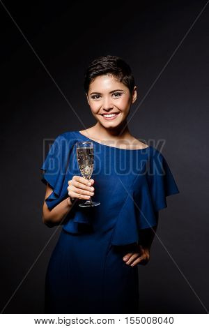 Young beautiful brunette girl in dark blue evening dress smiling, holding champaign glass, looking at camera at party over grey background. Copy space.