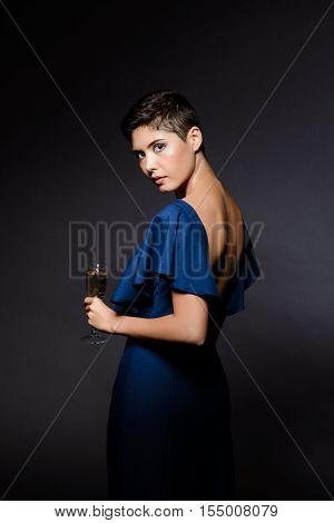 Young beautiful brunette girl in dark blue evening dress posing, holding champaign glass, looking at camera at party over grey background. Copy space.