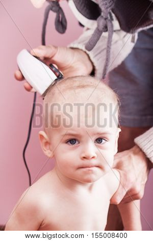 The father of the child cuts clipper. Family values
