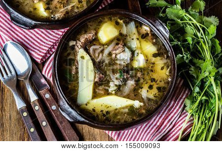 Chilean meat soup ajiaco. Latinamerican food. Ajiaco - traditional chilean soup with grilled meat, onion and potato served in clay plate from pomaire Chile