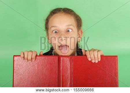 Beautiful school girl peeping from behind her red book. Pull a face. Isolated on green