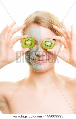 Skin care. Woman in clay mud mask on face covering eyes with slices of kiwi isolated. Girl taking care of dry complexion.