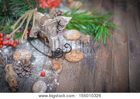 Christmas and New Year Decoration with Vintage Wooden Horse, Pine Branches, Oatmeal Cookies, Rowan, Walnuts, Fir Cones, on a Rustic Wooden Table